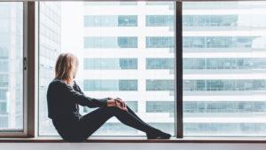 Frau sitzt am Fenster und guckt raus